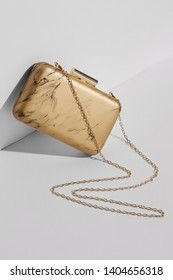 Front view shot of golden shoulder bag covered with leather with marble print and adorned with massive clasp fastener. The accessory with snake-like placed chain strap is angled on white platform.