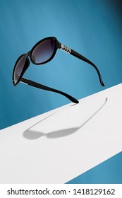 Front view shot of ink black oval-shaped sunglasses, adorned with silver criss-crossed insertions on ear-pieces. The tilted accessory is isolated in air against background with wide white stripe.