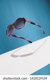 Front view shot of purple gradient oval-shaped sunglasses, adorned with silver criss-crossed insertions on ear-pieces. The tilted accessory is isolated in air on background with wide white stripe.