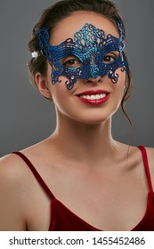 Front view shot of woman with tied back hair, wearing wine red crop top. The smiling girl is raising head, wearing blue asymmetric masquerade mask with perforation. Vintage themed night accessory.