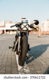 Front view of silver vintage custom motorcycle motorbike cafe racer on empty rooftop parking lot surrounded by urban environments midtown buildings. Hipster style, student dream, wild lifestyle.