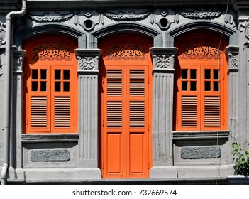 Front view of Singapore Straits Chinese or Peranakan shop house exterior with arched windows, antique orange wooden louvered shutters and ornate columns in the historic Little India area