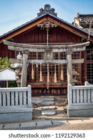 Front View of Small Town Shinto Shrine with Stone Torii Gate and Shimenawa Rope. Portrait Orientation, No people (Matsumoto, Japan).