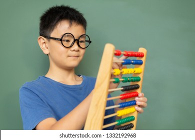 Front view of smart Asian boy learning math with abacus against green chalkboard in a classroom at elementary school