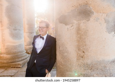 Front view of smiled young male in glasses, wearing in black suit, relying on column of builld, putting hand into pocket of pants and looking away