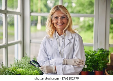 Front view of a smiling attractive female botanist in gloves looking in front of her