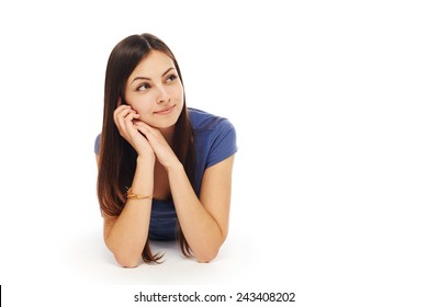 Front view of smiling beautiful woman lying on the floor over white background and looking to the side at blank copy space