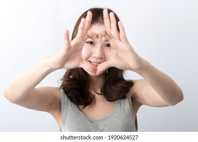 Front view of A smiling beauty young Asian lady with beautiful long hair. Young Asian woman with smiley face making a heart shape by her hands. Over white background. Symbol of love gesture concept.