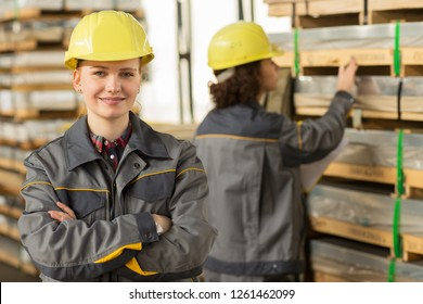 Front view of smiling blonde female warehouse worker in yellow helmet, with arm crossed. On background colleague, also wearing in uniform, with yellow folder counting by hand shells.