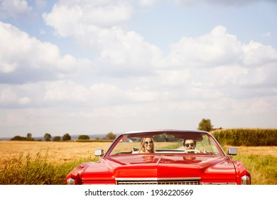 Front view of smiling couple in a red car