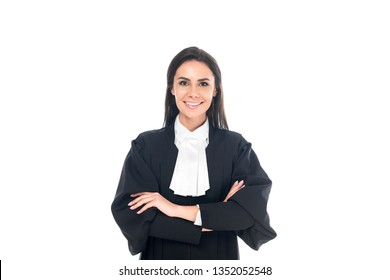 Front view of smiling judge in judicial robe standing with folded arms isolated on white