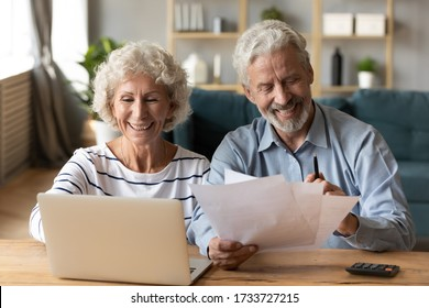 Front view smiling old woman entering payment data into banking application on computer while pleasant mature husband reading paper tax document. Happy senior married couple managing family budget.