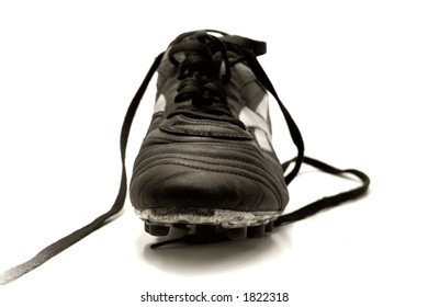 front view of a soccer shoe with dramatic lighting, studio style. Sepia-toned to create mood.