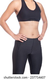 Front view of sport woman in black exercise attire with sport bra and lycra pants with hands on hip.