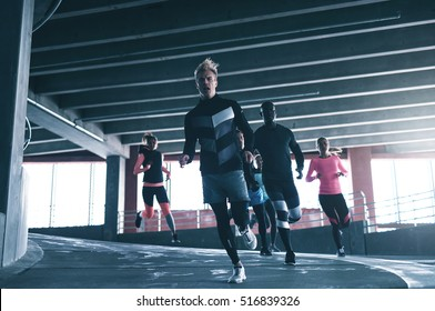 Front view of sportive man running towards camera with his team-mates. Copyspace