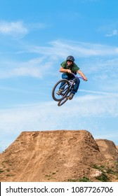 Front view of sportsman on mountain bike flying over hill in the nature