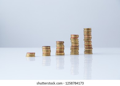 Front view of stacks of Euro coins in ascending order on light gray table and background. Simple and minimalistic design and style, selective focus. Concept photo of financial growth.