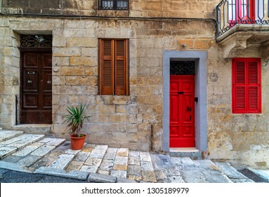 Front view of stone house with typical colorful wooden doors in Valletta, Malta.