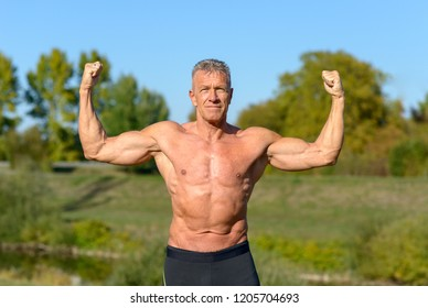 Front view of a strong man flexing his arms while standing in a park