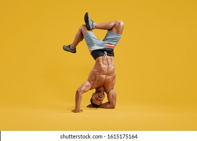 Front view of strong young man with naked torso standing upside down. Shirtless athletic gentleman holding handstand position. Isolated on yellow studio background. Concept of strength and endurance.