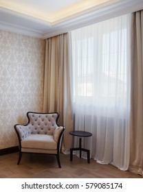 Front view of stylish armchair in classic style in corner of the room and rounded wooden table near. Light living room with big window on background, curtain in beige and brown colors.