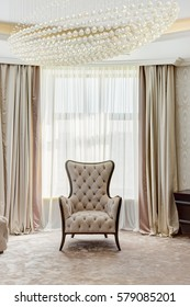 Front view of stylish cozy armchair in classic style. Light living room with big window on background, curtain in beige and brown colors. Room in white and beige colors.