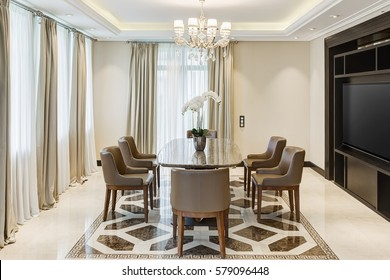Front view of stylish and light dining room with big windows and crystal chandelier in center of ceiling. Luxury interior of big room with wooden table in center and armchairs around.
