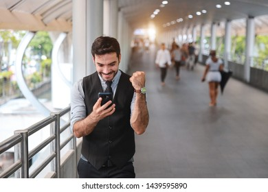 front view successful caucasian businessman in black suite who standing in walk way, he glad to receive a message from his cell phone that he is the winner from auction with happy smiling face