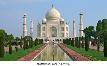 front view of Taj Mahal in late morning with clear blue sky and reflection in water