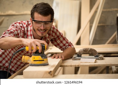 Front view of talented young carpenter machining lumber with help of special equipment. Professional woodworker holding yellow electric sander in hands. Bearded man wearing safety glasses.