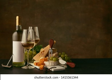 Front view of tasty cheese plate with grapes and the wine bottle, fruit and wineglasses on dark studio background, copy space to insert your text or image. Gourmet food and drink.