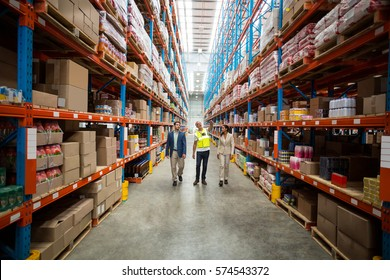 Front view of team is looking shelves and walking in a warehouse