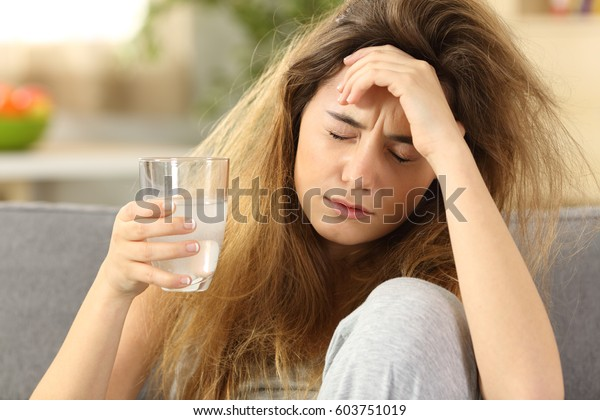 Front view of a teen with tousled hair suffering head ache sitting on a couch in the living room at home