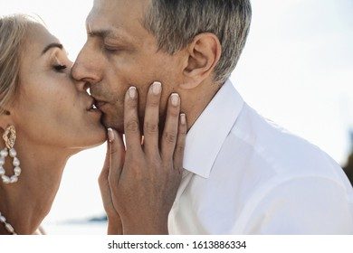 Front view of tender kiss of couple outdoors with closed eyes