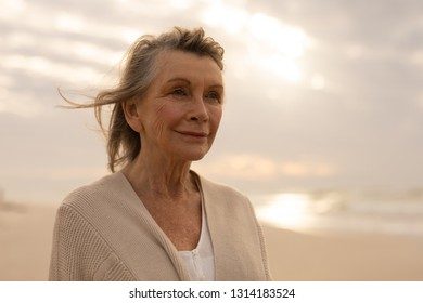 Front view of thoughtful senior Caucasian woman standing on the beach