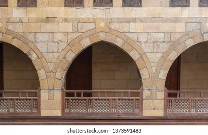 Front view of three arches with interleaved wooden balustrades at the arcade surrounding the courtyard of caravanserai (Wikala) of al-Ghuri, Medieval Cairo, Egypt