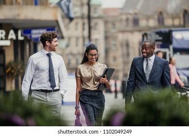 Front view of three business people walking through the city streets. All three people are wearing formal clothing.