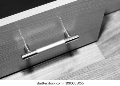 Front view of three closed sliding wooden drawers with metal long handles, object