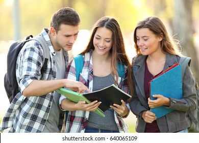 Front view of three students learning reading a notebook and commenting in the street