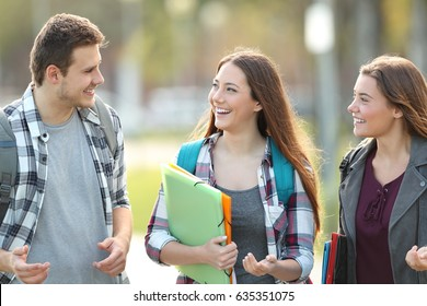 Front view of three students walking and talking in an university campus