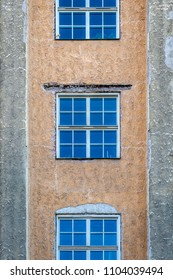 Front view of three symmetrical windows on a stone city building with colorful texture.