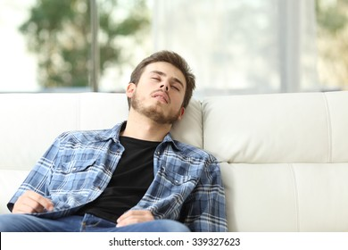 Front view of a tired man sleeping on a couch at home