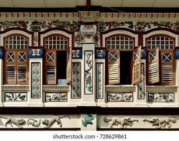Front view of traditional Peranakan Straits Chinese shophouse exterior with antique wooden louvered shutters, arched windows and ornate carvings in the Geylang District of Singapore