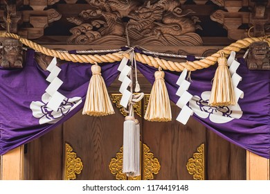 Front View of Traditional Shimenawa Rode with Shide Streamers and Purple Banner at Entrance to Historic Temple (Gifu, Japan).
