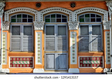 Front view of traditional Straits Chinese or Peranakan Singapore shop house exterior with arched windows, antique grey wooden shutters and colourful exterior in Balestier Road, Singapore