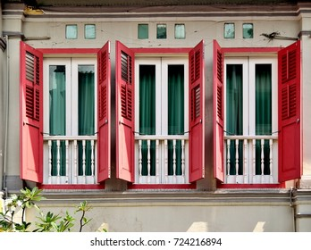 Front view of traditional vintage Chinese shop house exterior with antique red wooden louvered shutters and 'Juliet' balconies in downtown Singapore.