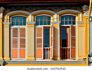 Front view of traditional vintage Peranakan or Straits Chinese Singapore shop house with arched windows and orange antique wooden shutters in historic Chinatown