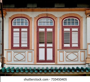 Front view of traditional vintage Peranakan or Straits Chinese shop house  exterior with ornate exterior, antique wooden louvered shutters and arched windows in historic downtown Singapore.
