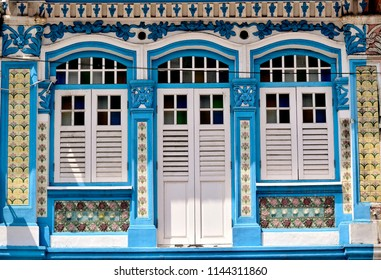 Front view of traditional vintage Singapore Straits Chinese or Peranakan shop house or shophouse with arched windows, antique wooden shutters and Chinese tiles in the historic Joo Chiat District.