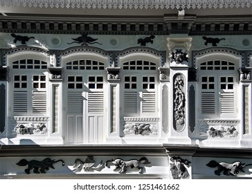 Front view of traditional vintage Singapore Peranakan or Straits Chinese shop house  exterior with antique white wooden shutters and ornate columns in the historic downtown area